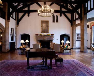 piano on a purple rug, chandelier hanging above