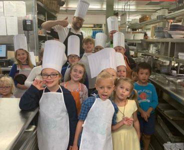 children dressed as chefs in kitchen